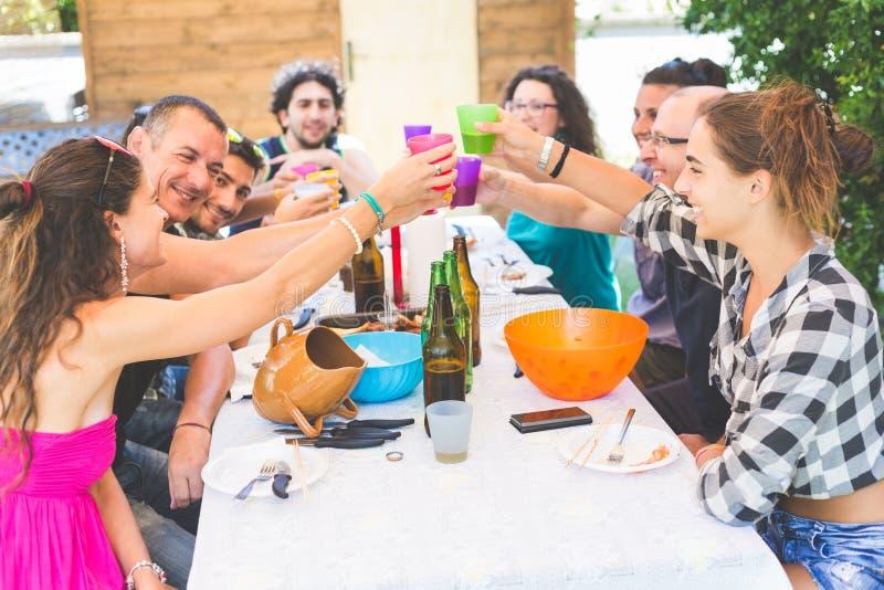 Groupe de personnes s'asseyant ayant le déjeuner ensemble et le grillage images stock