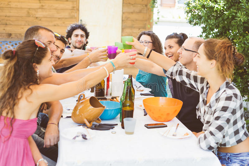 Groupe de personnes s'asseyant ayant le déjeuner ensemble et le grillage photographie stock