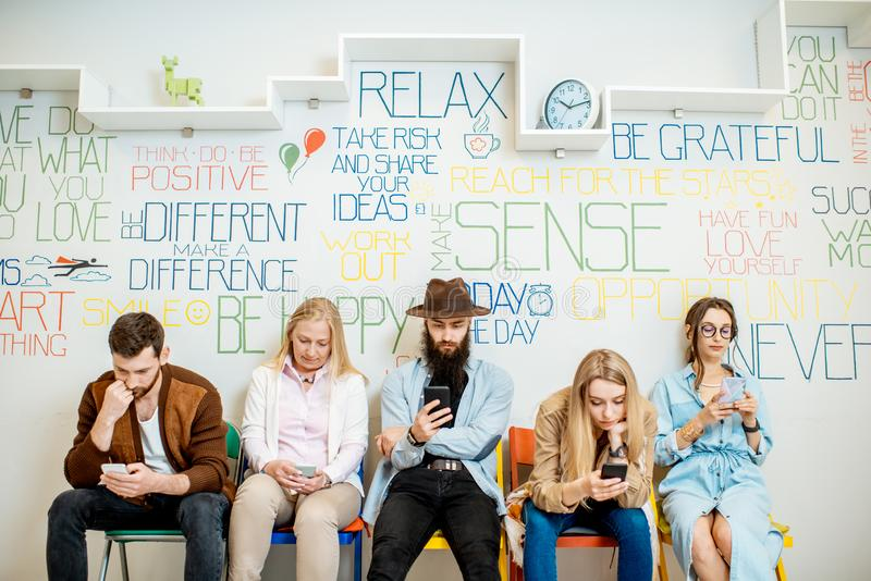 Groupe de personnes s'asseyant dans une rangée avec les téléphones intelligents à l'intérieur photo libre de droits