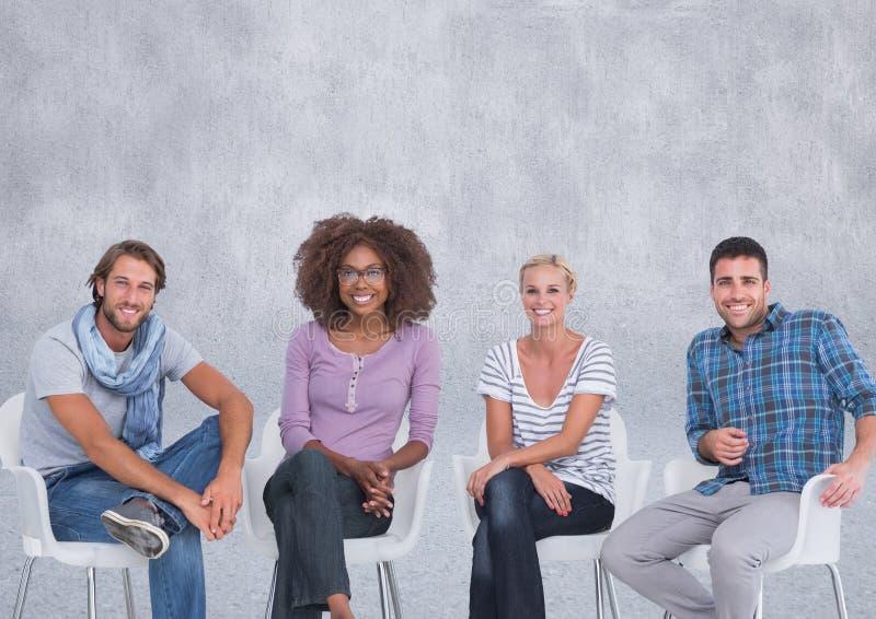 Groupe de personnes s'asseyant devant le fond gris photographie stock