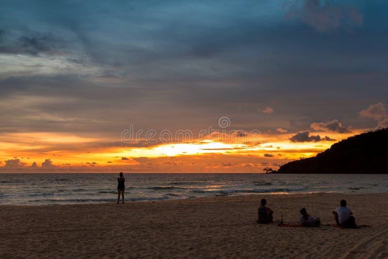 Groupe de personnes s'asseyant sur la plage et appréciant le coucher du soleil images libres de droits