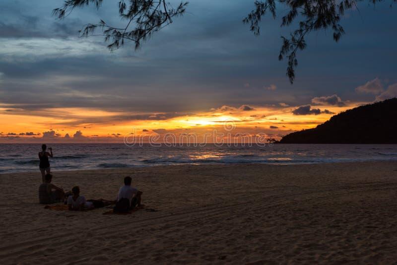 Groupe de personnes s'asseyant sur la plage et appréciant le coucher du soleil photo stock