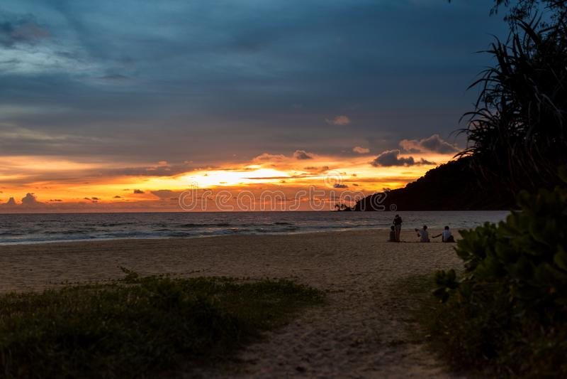 Groupe de personnes s'asseyant sur la plage et appréciant le coucher du soleil photographie stock libre de droits