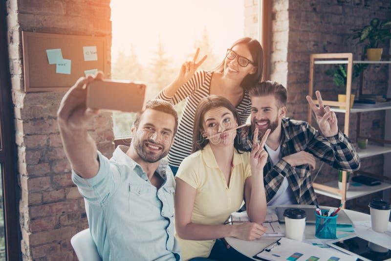 Groupe de personnes de sourire heureuses prenant un autoportrait dans un café W image stock