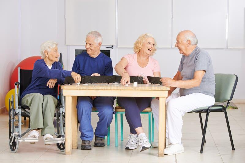 Groupe de personnes supérieures jouant le jeu de rami image stock