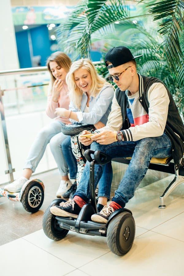 Groupe de personnes sur le hoverboard électrique de scooter se reposant au banc et à l'aide du téléphone photo stock