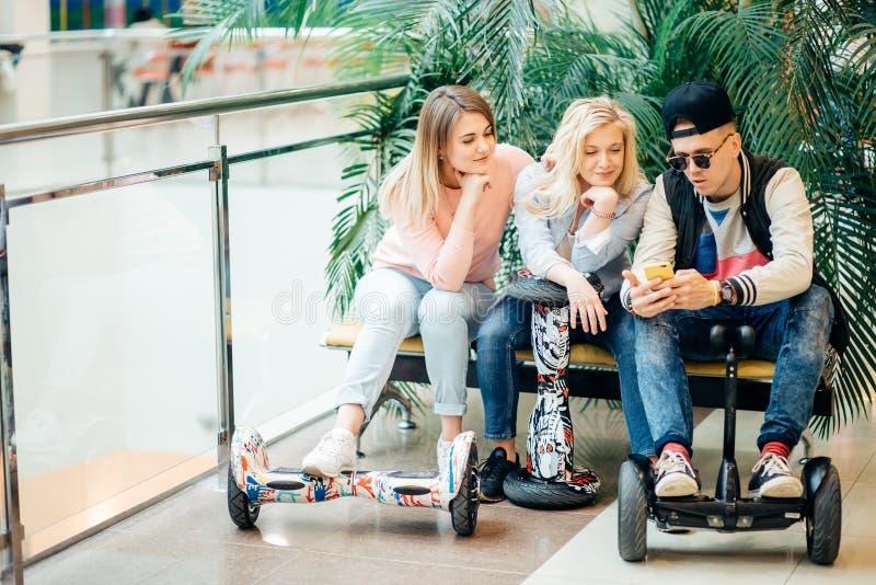 Groupe de personnes sur le hoverboard électrique de scooter se reposant au banc et à l'aide du téléphone photo libre de droits