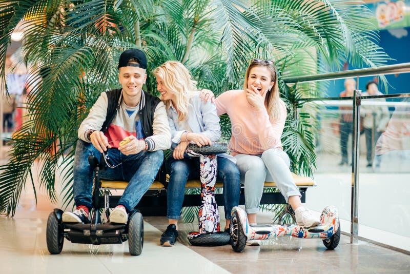 Groupe de personnes sur le hoverboard électrique de scooter se reposant au banc et à l'aide du téléphone photographie stock libre de droits