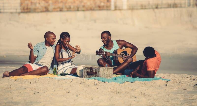 Groupe de personnes traînant à la plage images stock