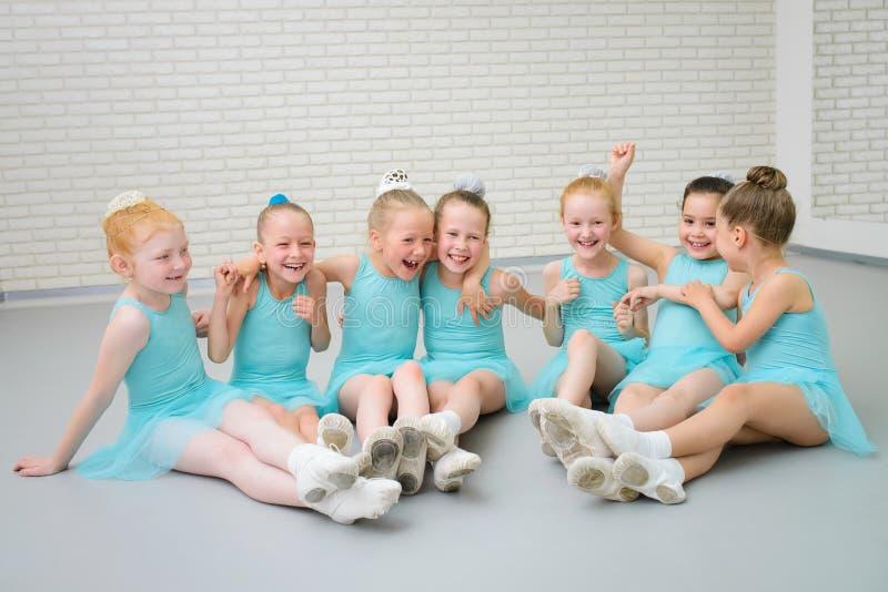Groupe de petits danseurs classiques mignons ayant l'amusement à la classe d'école de danse image stock