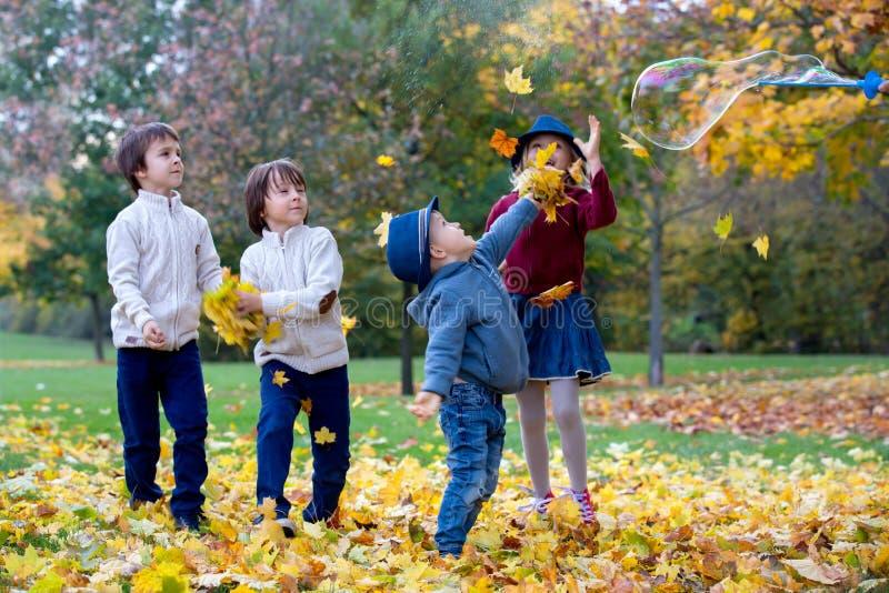 Groupe de petits enfants en parc, ayant les feuilles de lancement d'amusement photos stock