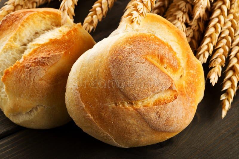 Groupe de petits pains cuits au four entiers et frais de blé avec des oreilles de blé sur W foncé images libres de droits