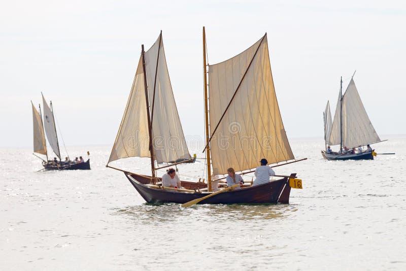 Groupe de petits, vieux bateaux de navigation avec l'équipage féminin photographie stock