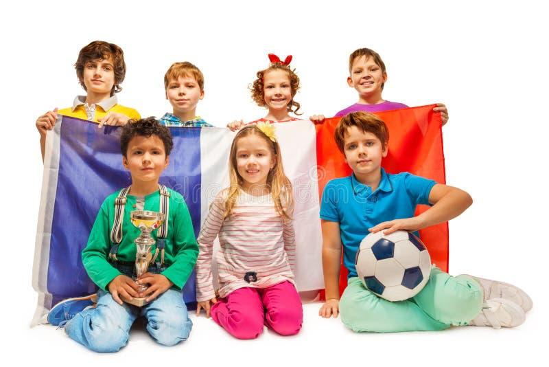 Groupe de peu de passionés du football tenant le drapeau français photographie stock