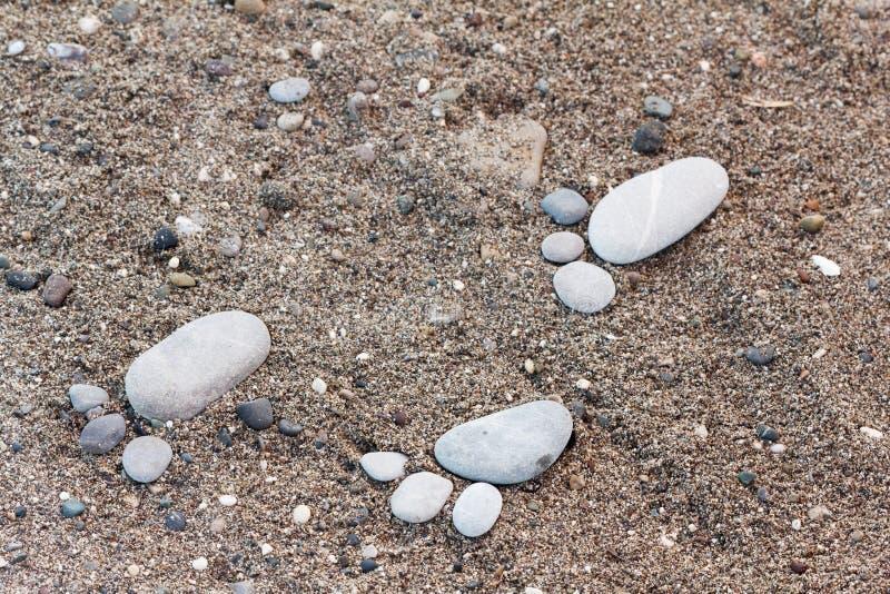 Groupe de pied par le caillou sur le fond de sable images libres de droits