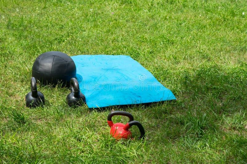 Groupe de poids s'exerçants de forme physique sur l'herbe verte photo stock