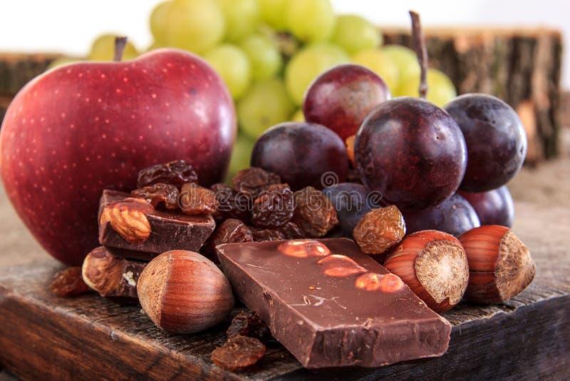 Groupe de pommes et de raisins de fruit avec du chocolat nuts photo stock