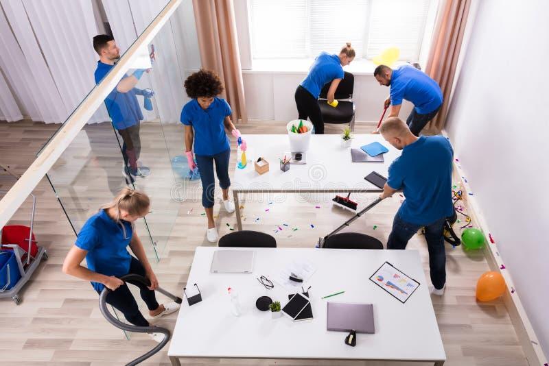 Groupe de portiers nettoyant le bureau avec l'équipement de nettoyage image libre de droits
