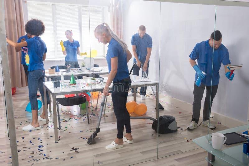 Groupe de portiers nettoyant le bureau photo stock