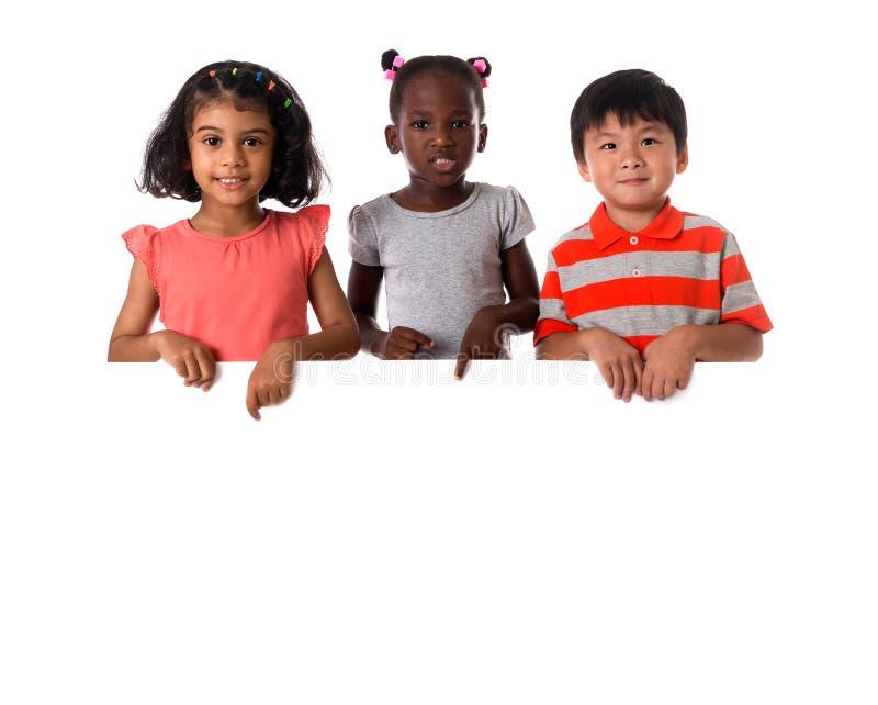 Groupe de portrait multiracial d'enfants avec le conseil blanc photo libre de droits