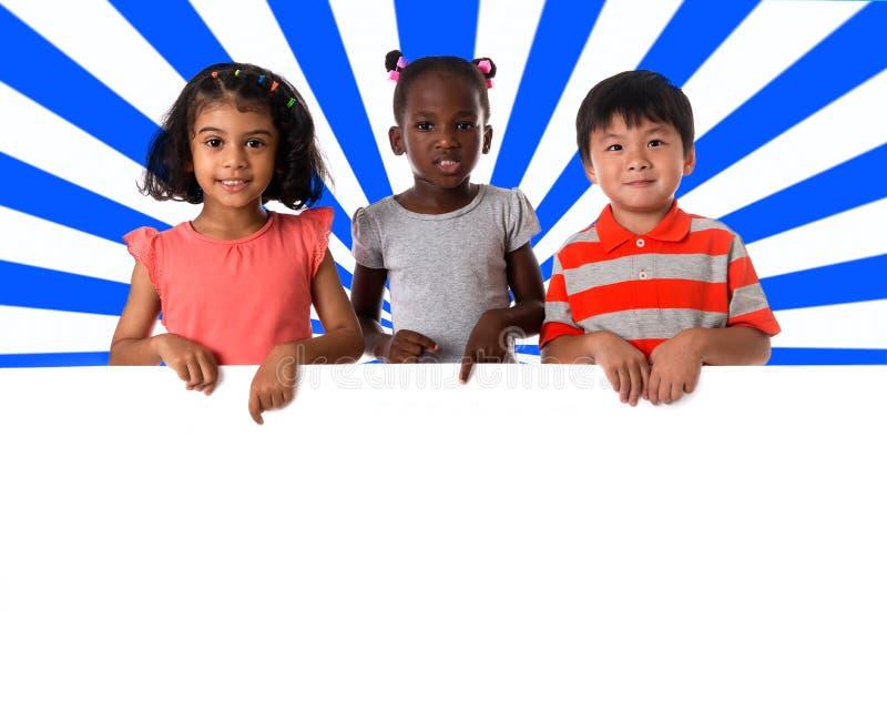 Groupe de portrait multiracial d'enfants avec le conseil blanc photos libres de droits