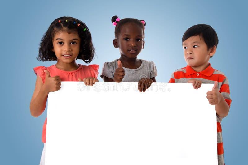 Groupe de portrait multiracial d'enfants avec le conseil blanc image libre de droits
