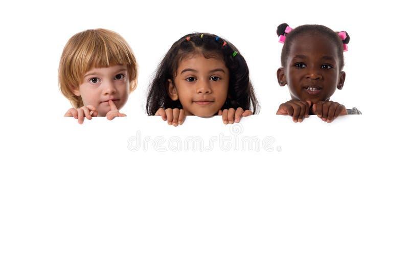 Groupe de portrait multiracial d'enfants avec le conseil blanc D'isolement image stock