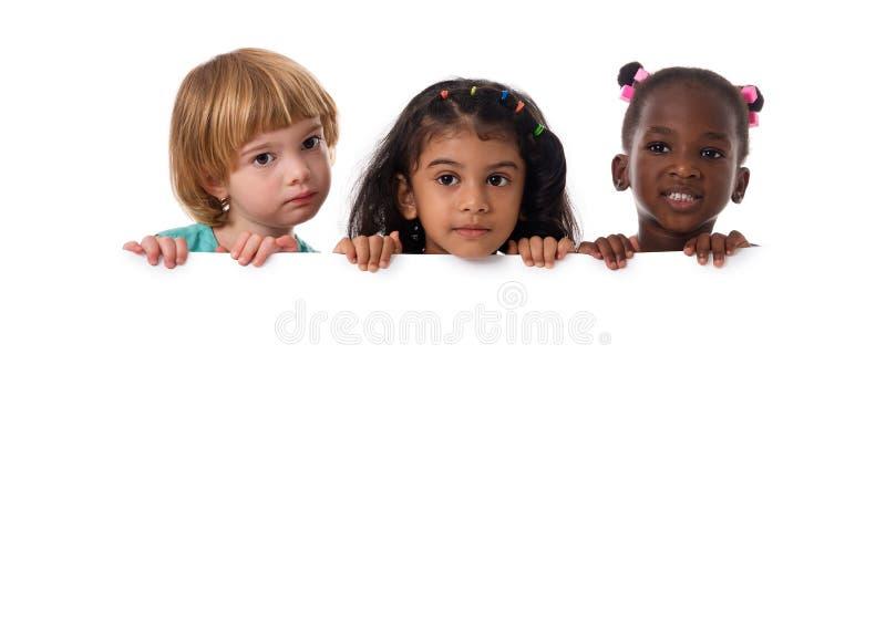 Groupe de portrait multiracial d'enfants avec le conseil blanc D'isolement image libre de droits