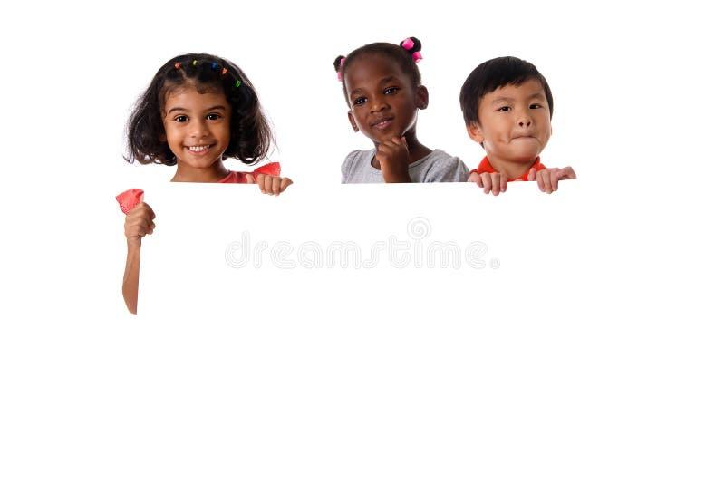 Groupe de portrait multiracial d'enfants avec le conseil blanc D'isolement images stock