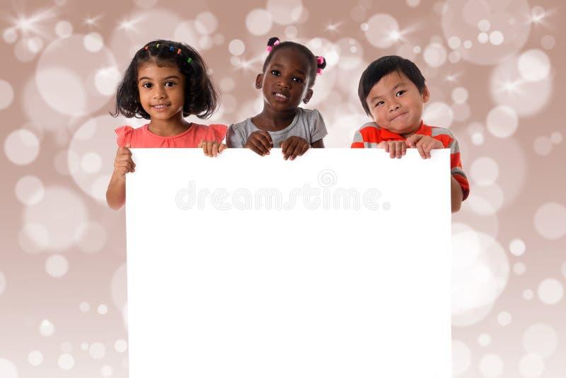 Groupe de portrait multiracial d'enfants avec le conseil blanc D'isolement photographie stock
