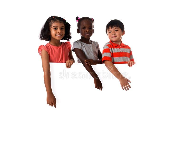 Groupe de portrait multiracial d'enfants dans le studio avec le conseil blanc D'isolement images stock