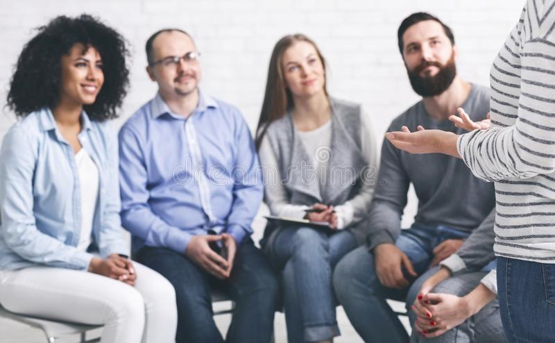 Groupe de réadaptation écoutant la femme se présentant à la thérapie photographie stock