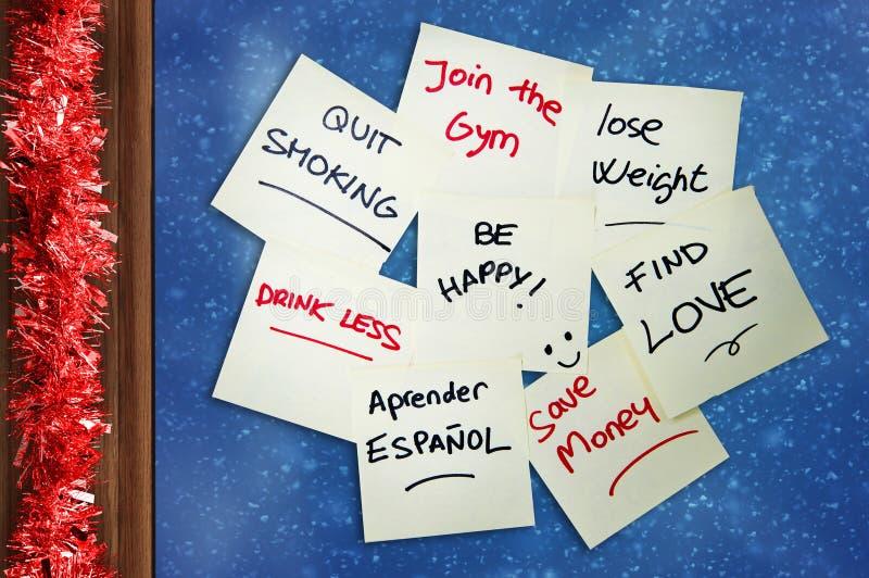 Groupe de résolutions de nouvelle année écrites sur la pile de notes de post-it sur la tresse de Noël de cadre de verre de fenêtr images libres de droits