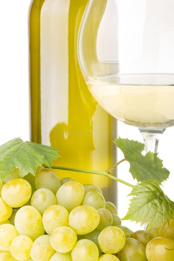 Groupe de raisins blancs avec la vigne, verre de vin et bouteille sur le fond blanc photographie stock libre de droits