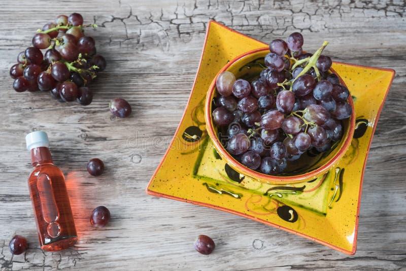 Groupe de raisins rouges dans la cuvette orange, sur le fond en bois image libre de droits