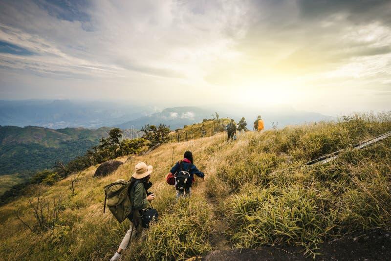 Groupe de randonneurs marchant sur une montagne au coucher du soleil le touriste de l'Asie de jeune homme à la montagne observe photographie stock libre de droits