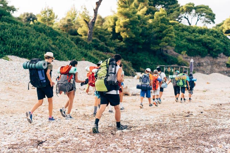 Groupe de randonneurs marchant sur une route arénacée le long du bord de mer images stock