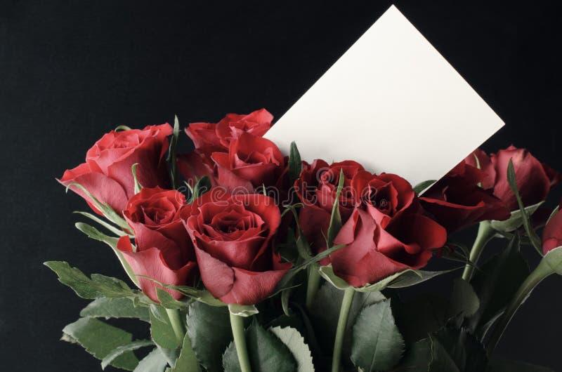 Groupe de roses rouges avec la carte blanche vierge de message photo libre de droits