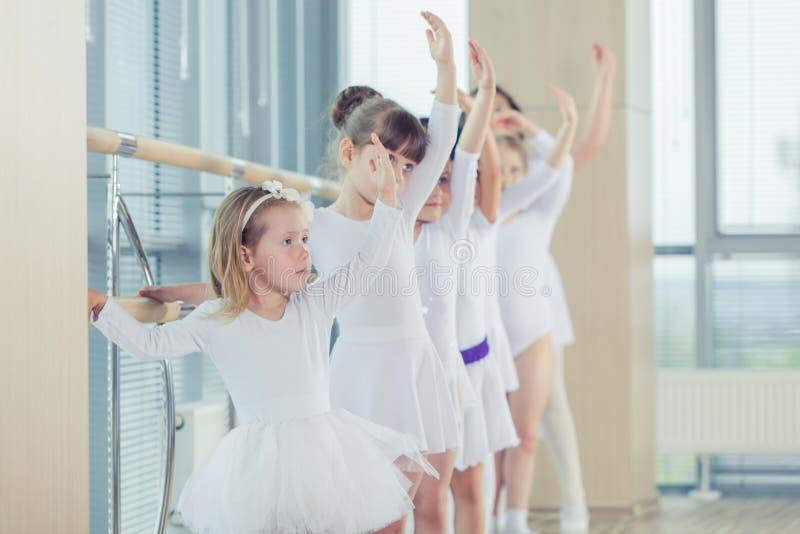 Groupe de sept petites ballerines se tenant dans la rangée et le ballet de pratique utilisant le bâton sur le mur photo libre de droits