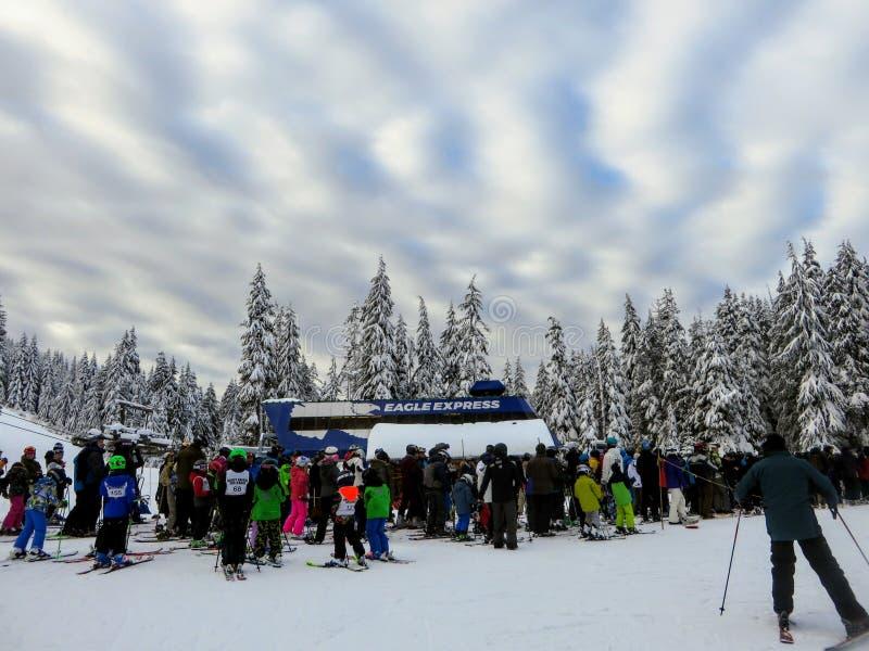 groupe de skieurs et de surfeurs attendant dans la ligne pour accrocher un tour vers le haut du remonte-pente sur la montagne de  photos libres de droits