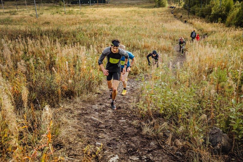 Groupe de skyrunners de coureurs des hommes courant la traînée ascendante dans l'herbe photographie stock libre de droits