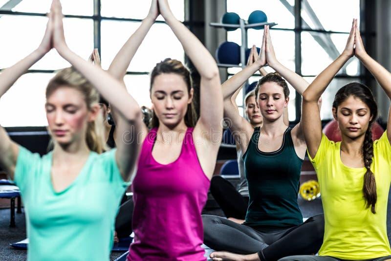 Groupe de sourire convenable faisant le yoga photographie stock