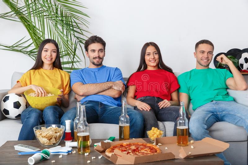 Groupe de supporters d'amis regardant la rencontre dans des chemises colorées décontractées photo stock