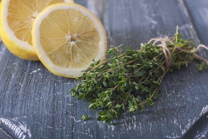 Groupe de thym et de citron organiques frais sur une surface en bois images stock