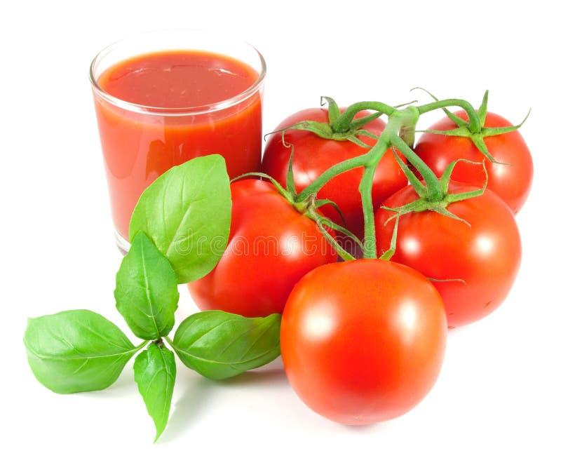 Groupe de tomates fraîches avec les feuilles de basilic et le verre de jus de tomates photo libre de droits