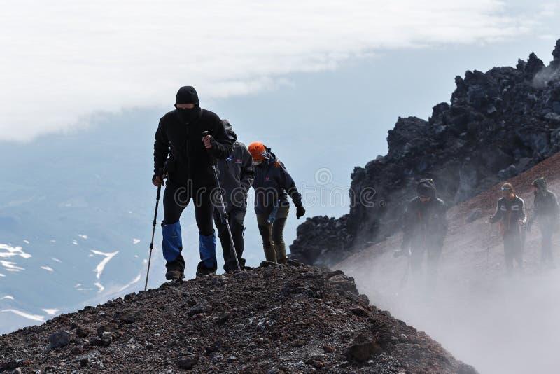 Groupe de touristes s'élevant pour compléter le cratère du volcan actif photographie stock libre de droits