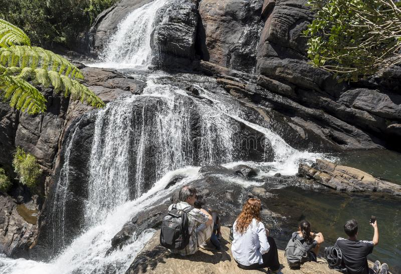 Groupe de touristes s'asseyant sur les roches près de la cascade au parc national image libre de droits