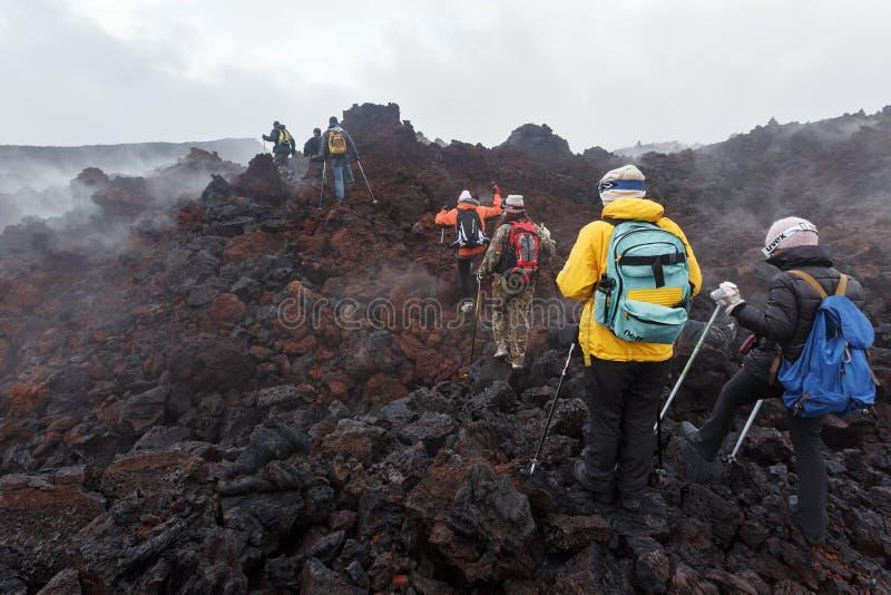 Groupe de touristes trimardant sur le volcan de Tolbachik d'éruption de gisement de lave kamchatka images stock