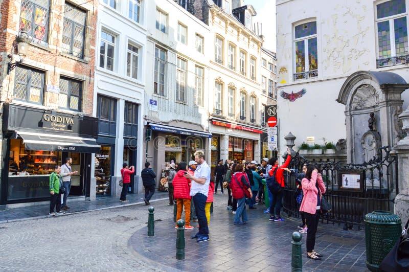 Groupe de touristes visitant Manneken Pis ou le petit pipi d'homme situé près de Grand Place dans la ville de Bruxelles, Belgique photographie stock