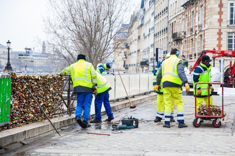 Groupe de travailleurs enlevant des cadenas chez Pont Neuf à Paris photographie stock